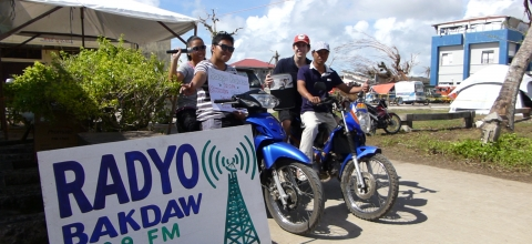 "4 people on motorbikes sit next to a large sign saying ""Radyo Bakdaw"""