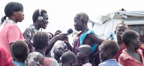 A journalist interviews a woman while a group of children look on.