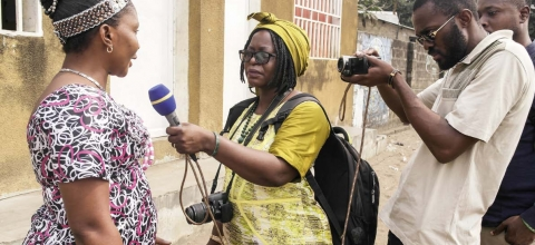 A woman reporter interviews a woman while a man videotapes.