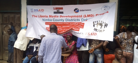 "A group of people stand around a banner that says, ""Liberia Media Development Program"""