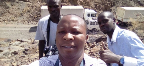 A man takes a selfie with two other men behind him.