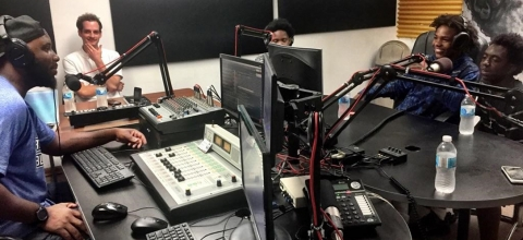 5 young men sit in a radio studio