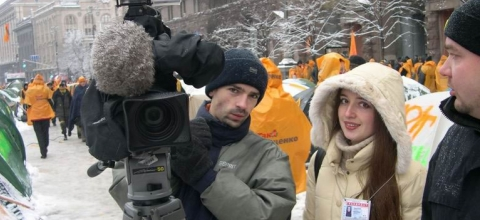 A cameraman and a Journalist stand next to each other on a snowy street