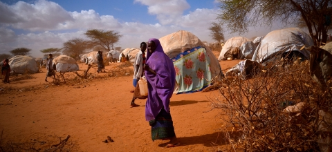 A woman carrying a water jug walks by a tent in Dadaab refugee camp