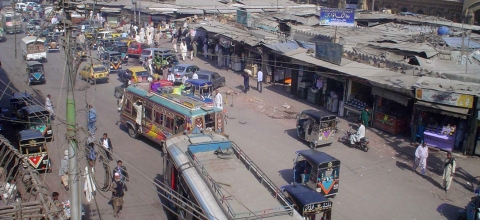 A street in Karachi crowded with cars, buses, tuk-tuks and pedestrians
