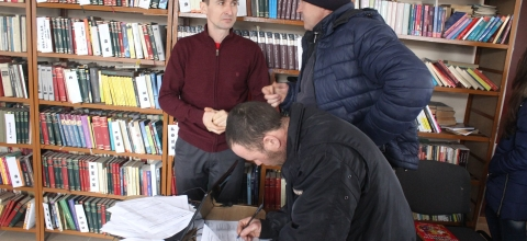 Alexandru stands by a bookshelf in the library talking to a man; another man sits at a table next to them.