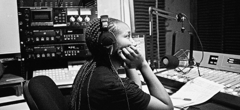 A woman sits at a mic in a radio studio