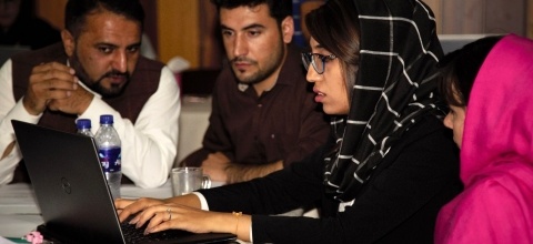 A woman types on a laptop, while two men and another woman watch.
