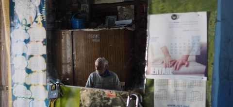 A man sits in a booth selling papers