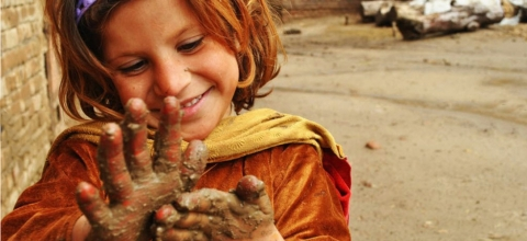 A little girl plays with mud on her hands