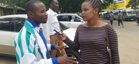 A woman interviews a man outside on a street