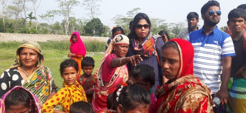 A group of women and children dressed in colorful clothing stand outside.