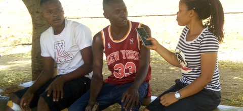 A woman reporter sits on a bench interviewing two young men