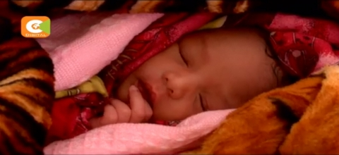 A baby sleeps covered by blankets