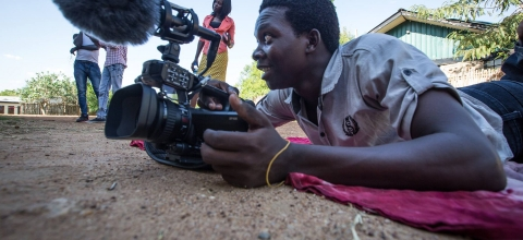 A man lies on the ground holding a video camera