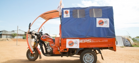 "A red 3 wheeled motorbike with ""Boda Boda"" flyers attached to it"