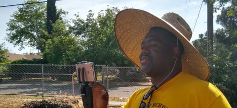 A man wearing a straw hat and standing next to a field, holds up his smartphone