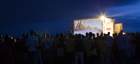 A crowd of people watch a movie being projected on the side of a truck