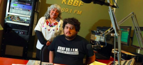 A man sits in a radio studio, a woman stands behind him