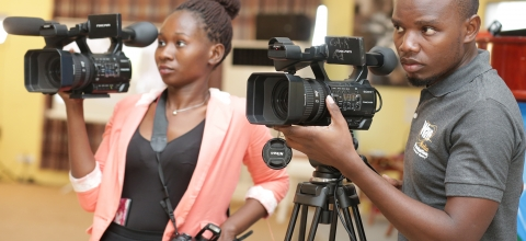 A young woman and a young man look through video cameras