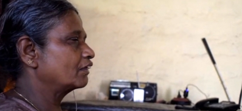 A blind woman sits next to her radio