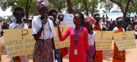 A woman journalist stands holding a mic in front of a group of children holding posters