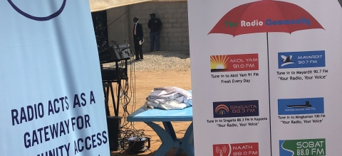 "Two large posters are set up next to a table outside. One says, ""Radio acts as a gateway for community access to information."""