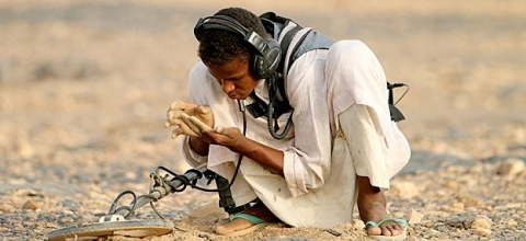 A man crouches on a sandy expanse, holding an electronic device