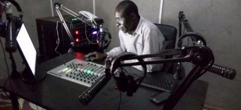 A man looks at a computer screen in a radio studio