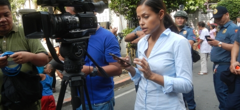 3 journalists stand in the street with a video camera; police stand behind them