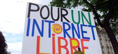 "A man holds up a sign saying, ""Pour un Internet libre"""