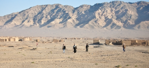 Four people stand apart from each other on a dusty road. Houses and mountains are in the background.