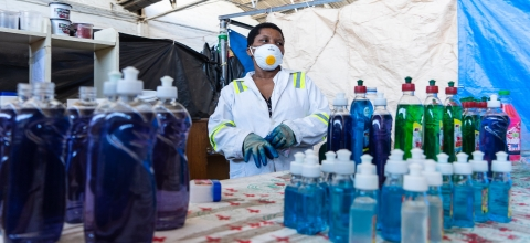 A woman wearing a mask stands behind a table loaded with bottles of detergent and sanitizer