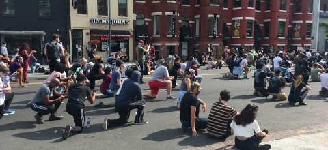 A large group of people kneel on one knee in a commercial street