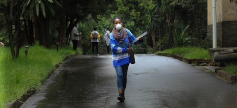 A woman wearing a mask walks down the middle of a road