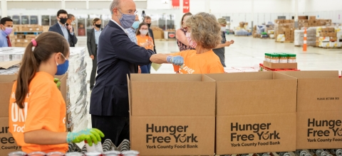 "People wearing masks stand around boxes labeled ""Hunger Free New York"""