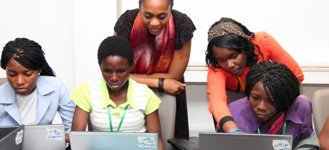 3 women work at laptops while two women stand behind them
