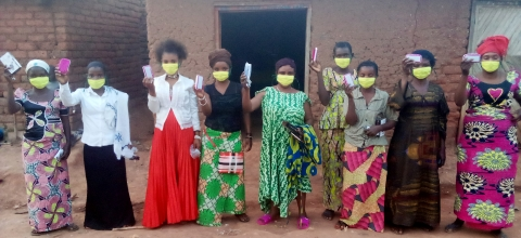 A group of women stand in a semi-circle wearing masks and holding small boxes