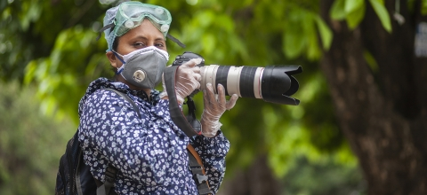 A woman wearing a mask and gloves holds a large camera