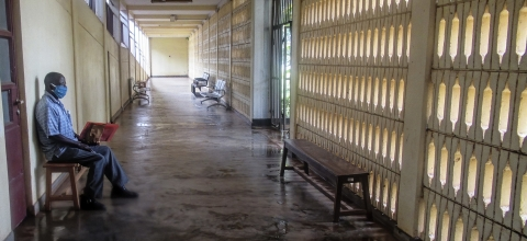 A man wearing a mask sits in an empty corridor in a hospital