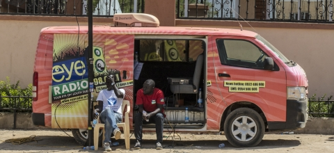 Two men sit in the open door of an Eye Radio van - with tall buildings in the background