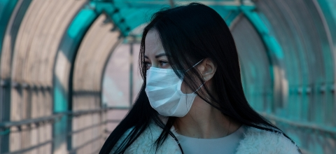 A woman wearing a face mask stands in a railway station