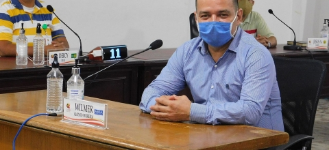 Two men wearing masks sit at tables with mics in front of them