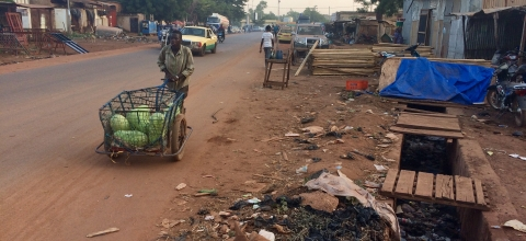 A man pushes a wagon down a street in Mali