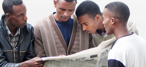 Four men read one newspaper together