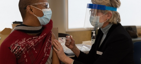 A man wearing a face mask gets an injection by a woman wearing a face mask