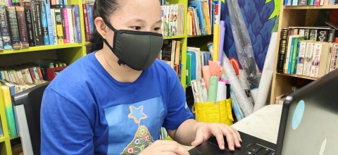 A young woman wearing a mask types on a laptop computer