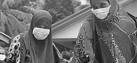 Two women wearing scarves and face masks walk together