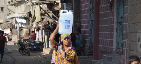 A woman walks down a street with a plastic jug of water on her head.