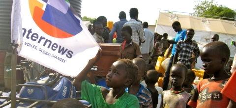 Children gather around a quad bike with an Internews flag on it.